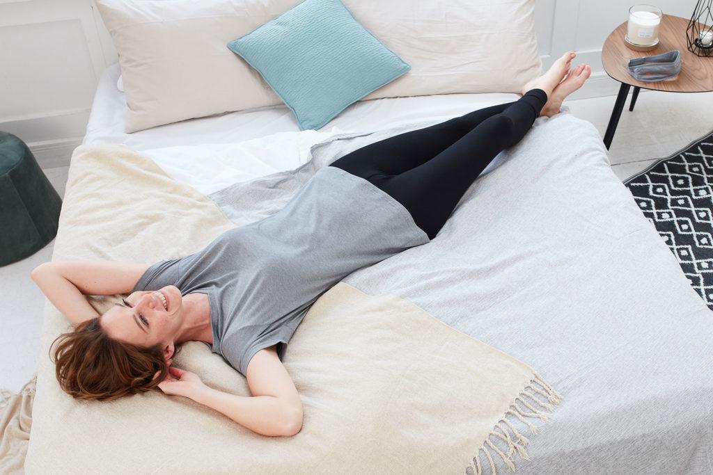 Frau liegt mit der Genki Vital Schlaf- und Regenerationsbekleidung auf einem Bett und genießt Entspannung