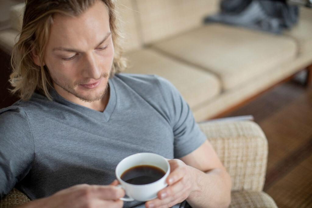 Mann trinkt Kaffee und trägt Genki Vital Regenerationsbekleidung zur Regeneration.